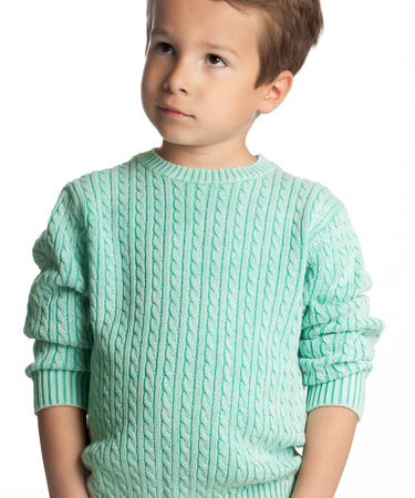 Stylish five year old European boy posing isolated over white studio background in knitted pullover. Fashion child. Confident little boy.