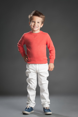 five year old: Friendly little five year old boy posing over gray background.