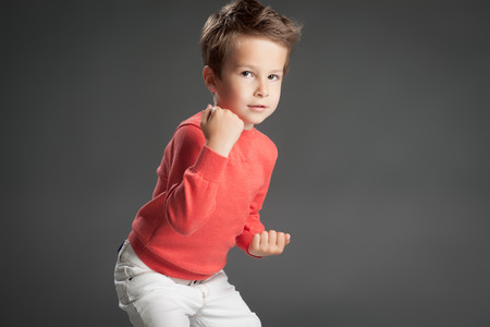 five year: Confident five year old boy in fighting posture over gray background.