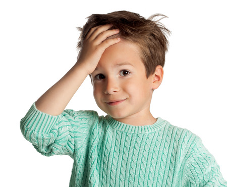 Stylish five year old European boy posing over white studio background. Stunned surprised expression on child face. Face palm gesture.