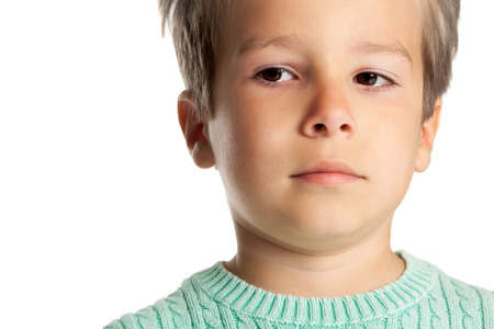five year old: Sad five year old boy posing over white studio background. Closeup of child face in tears. Stock Photo