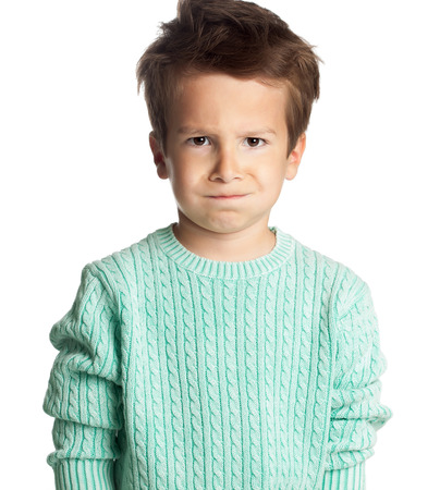 Angry five year old European boy posing over white studio background.