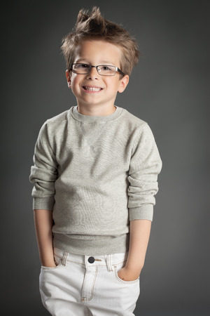 Handsome five year old boy posing in studio over gray background. Boy wearing reading glasses. Banco de Imagens - 40875950