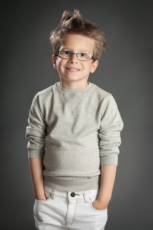 cool people: Handsome five year old boy posing in studio over gray background. Boy wearing reading glasses.