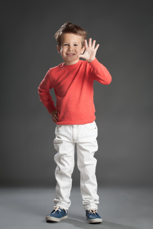 Friendly little five year old boy doing greeting gesture.