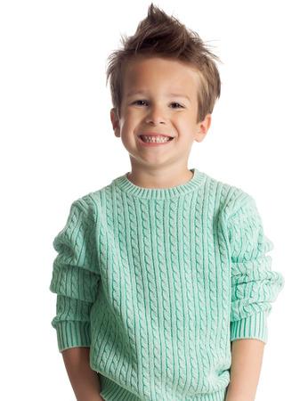 sueteres: Cinco años Niño feliz Europeo de edad que presenta sobre el fondo blanco del estudio. Niño con gran sonrisa. Foto de archivo