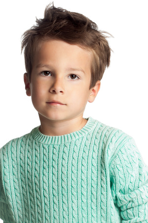 stylish boy: Stylish five year old European boy posing isolated over white studio background in knitted pullover. Fashion child. Confident little boy.