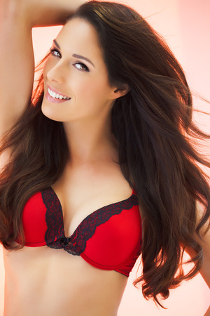 red bra: Beautiful woman with long dark hair posing in red bra over glowing background. Stock Photo