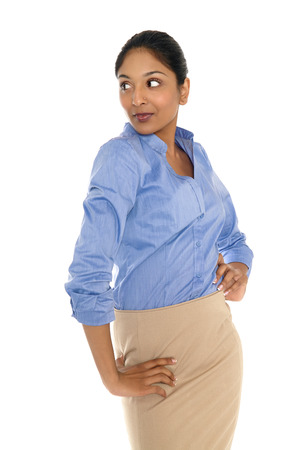 Young Indian businesswoman posing on white background wearing blue shirt and beige skirt.