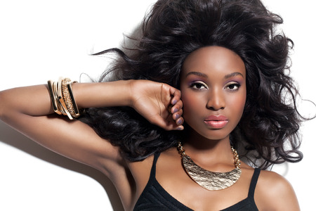 jewellery: Beautiful African fashion model with long lush hairstyle and makeup. African beauty and golden jewelry.