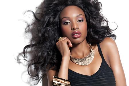 Mooie Afrikaanse fashion model met lange weelderige kapsel en make-up. Afrikaanse schoonheid en gouden sieraden.