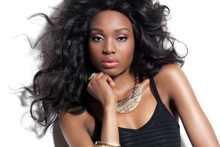 fashion: Modelo de forma Africano bonita com penteado exuberante longo e maquiagem. Beleza Africano e jóias de ouro.