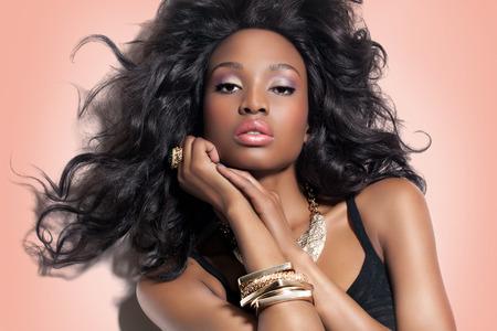 Modelo de manera africano con larga exuberante peinado y maquillaje. Belleza africana y joyas de oro.