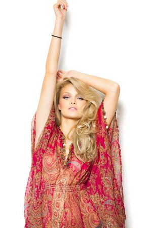 bikini bottom: Beautiful blond girl with long hair in red silk summer tunic and bikini bottom posing over white wall.