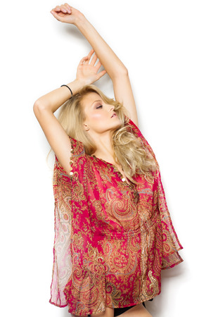 tunic: Beautiful blond girl with long hair in red silk summer tunic and bikini bottom posing over white wall.