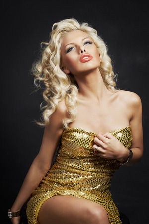 sequin: Beautiful blonde woman in golden sequin dress on dark grey background.
