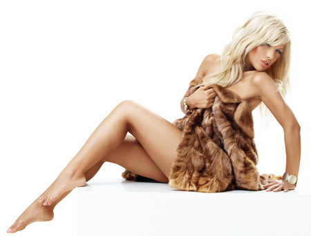 Young tanned blond woman with bare legs wrapped in mink coat.