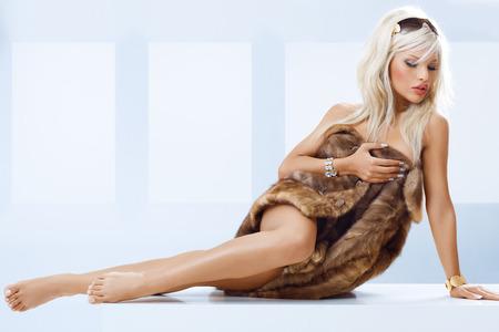 visone: Giovane donna bionda abbronzata con le gambe nude avvolte in pelliccia di visone. Archivio Fotografico