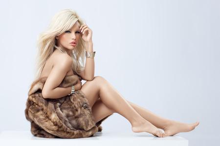 visone: Giovane donna bionda con le gambe nude avvolte in pelliccia di visone. Archivio Fotografico