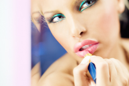 blonde females: Woman fixing her make-up with lipstick at mirror.