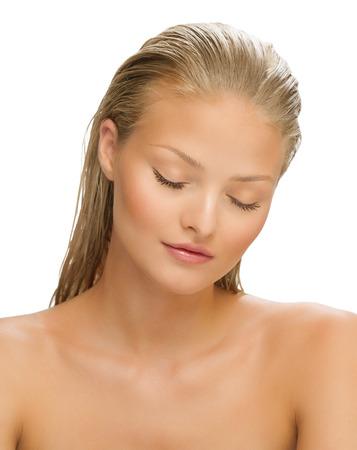 rubia ojos azules: Mujer joven con los ojos cerrados sobre fondo blanco. Piel bronceada hermosa. Sol de verano y las camas de bronceado. Foto de archivo