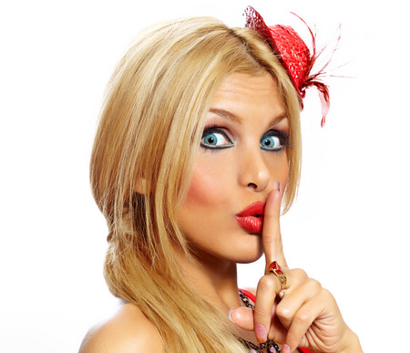 secrecy: Blonde model with small red cap making a secrecy sign. Stock Photo