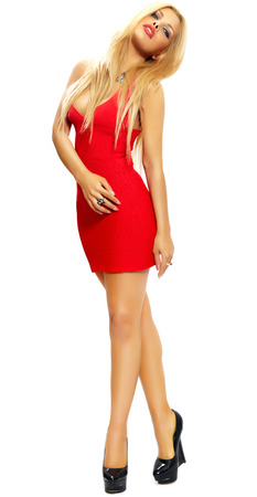 bombshell: Blonde woman in red mini-dress on white background. Stock Photo
