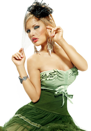 voile: Woman dressed in green velvet dress and small retro hat with veil. Retro style fashion over white background. Stock Photo