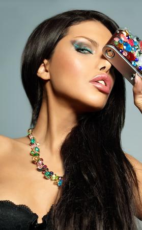 black hair blue eyes: Beautiful woman with bejeweled vintage camera.