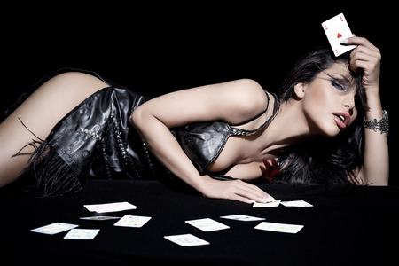 woman holding card: Woman laying down with cards.