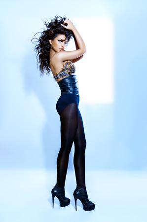 black hair blue eyes: Young woman wearing a black outfit with leather and feathers. Stock Photo