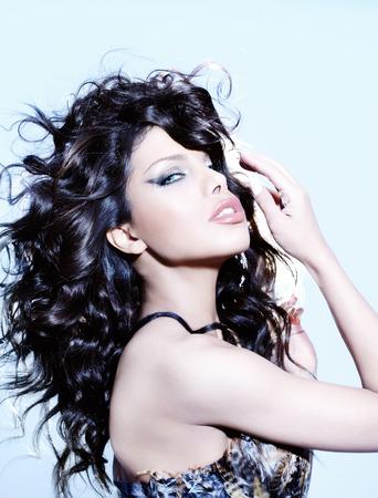 ojos negros: Mujer joven con el pelo negro exuberante sobre fondo azul. Foto de archivo
