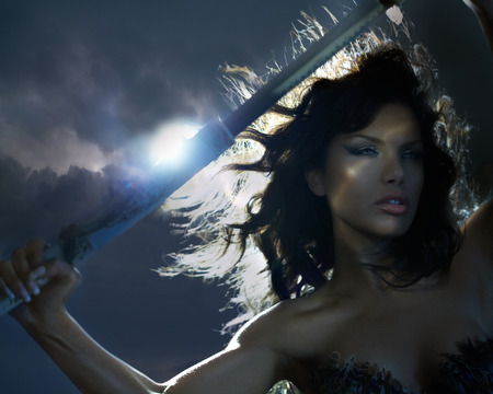 fashion photography: Beautiful woman in stormy weather holding a sword.