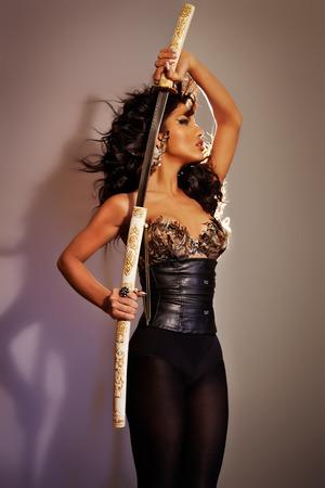 fantasy sword: Warrior woman posing with a sword. Stock Photo