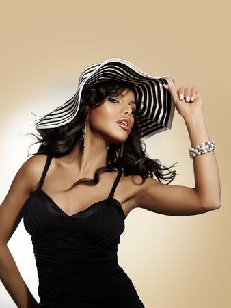 modelos negras: Mujer joven que llevaba un gran sombrero en el fondo beige.