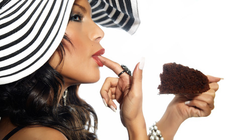 finger licking: Closeup of a woman in large hat licking her finger and holding a piece of chocolate pie. Stock Photo