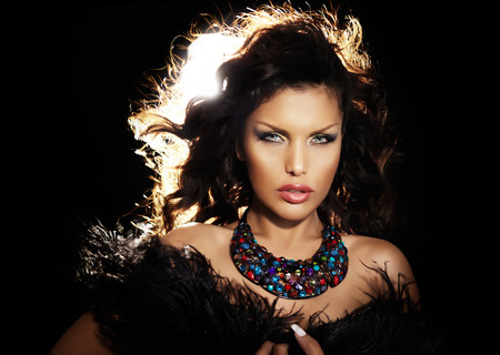 Beautiful woman wearing feathers and jewelry with her hair backlit. Banco de Imagens - 42091518