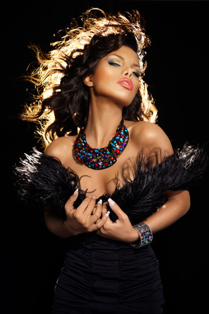 Beautiful woman wearing feathers and jewelry with her hair backlit.