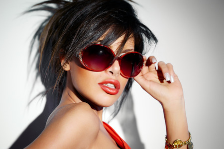 woman hairstyle: Woman wearing bright red sunglasses, lipstick and dress. Stock Photo