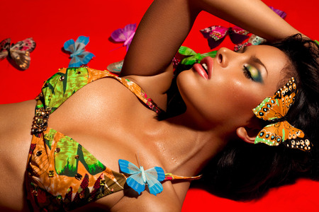laying down: Beautiful woman with wet skin in summer bikini covered in butterflies.