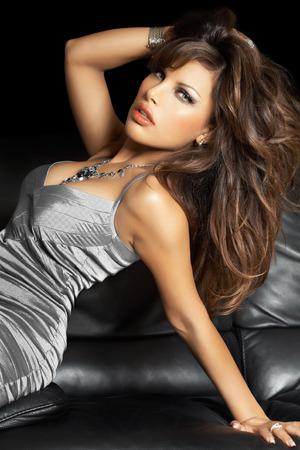 traje de gala: Mujer hermosa que presenta en vestido de seda de plata en el sofá de cuero. Foto de archivo
