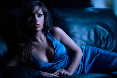 slight: Gorgeous model in dark room on leather sofa. Slight grain.