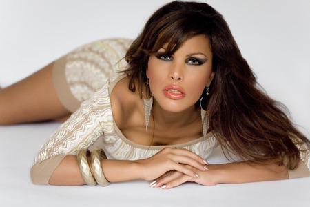 Model with long dark hair posing on floor.