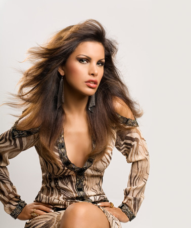 animal hair: Model with long dark hair wearing a tunic with animal print.