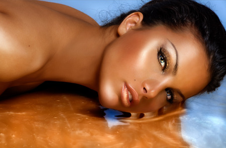 tanned: Beautiful model sinking in golden substance. Stock Photo