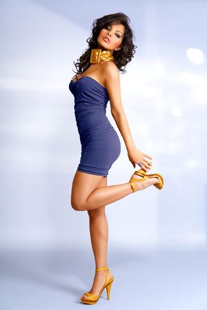 Muchacha en mini vestido azul sobre fondo azul claro.