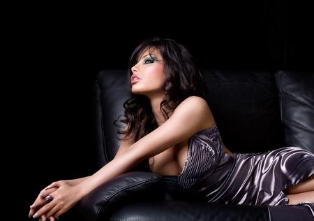 Beautiful model in gala dress laying on sofa. Banco de Imagens