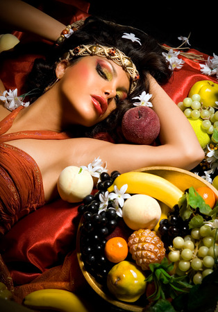 woman laying down: Woman laying down surrounded by fruit and flowers.