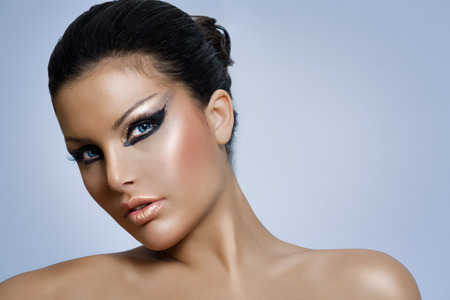 Model with expressive make-up and blue eyes.