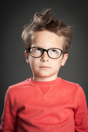 Five year old boy in glasses rolling eyes. Studio shot portrait over gray background. Fashionable little boy.